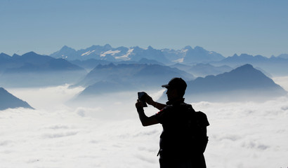 A man takes a picture with his smartphone during sunny autumn weather near the peak of Mount Rigi