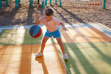 A girl playing with a basketball at a park.