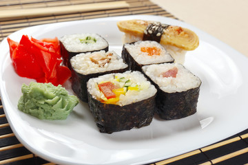 Sushi and rolls with ginger and wasabi on a black bamboo mat close up.