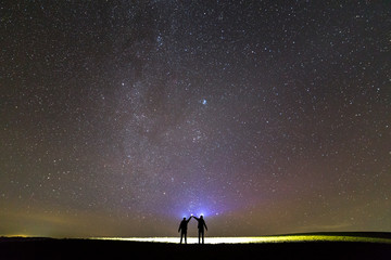 Back view of two men with head flashlights on green grassy field under dark blue summer starry sky.