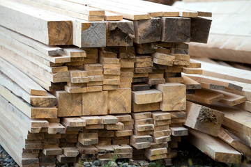 Close-up of piled stack of natural brown uneven rough wooden boards lit by bright sun. Industrial timber for carpentry, building, repairing and furniture, lumber material for construction.