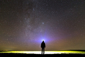 Black silhouette of man with head flashlight on grassy field under beautiful dark summer starry sky.