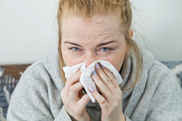 Young woman sick in bed wearing sweater. Illness