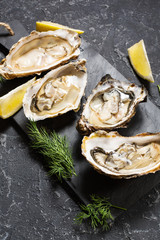 Opened Oysters with lemon on dark stone background