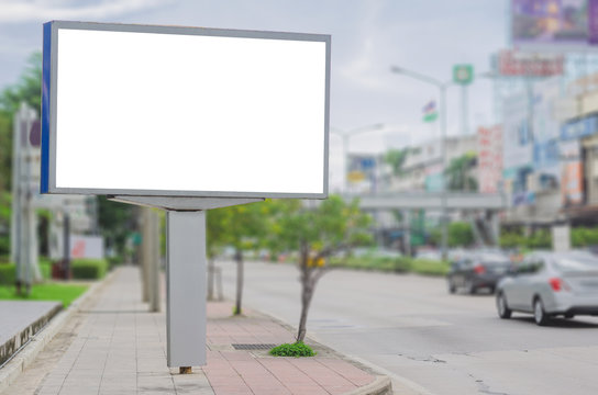 big blank billboard white LED screen horizontal outstanding in the city on pathway side the road traffic for display advertisement text template promotion new brand at outdoor with green tree.