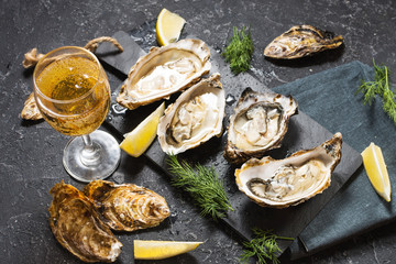 Opened Oysters and glass of white wine on dark texture background