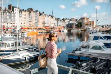 Young woman tourist enjoying beautiful view on the harbour traveling in Honfleur town in Normandy, France Fototapete