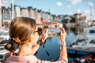Young woman tourist enjoying beautiful view on the harbour traveling in Honfleur town in Normandy, France