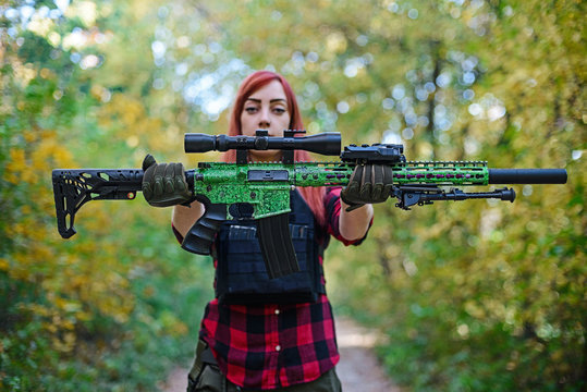 Young woman demonstrates a rifle with telescopic sight