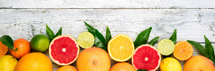 Citrus fruits background. Assorted fresh citrus fruits with leaves. Long web format. Top view Fototapete