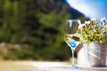 Glass of chilled white wine on a rocky mountain background. Hiking in Dolomites, Italy