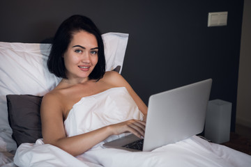 Woman working on laptop computer while lying on a bed at home.