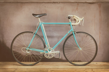 Vintage seventies light blue racing bicycle on a wooden floor