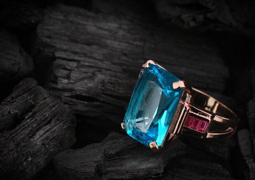 Jewelery ring with aquamarine gemstone on dark coal background, copy space