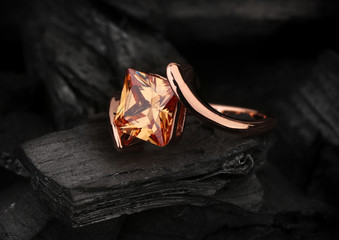 jewelry ring with big topaz gem on black coal background