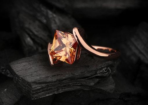 jewelry ring with big topaz gem on black coal background