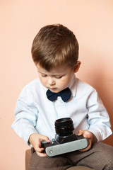 Little boy with aged retro camera. Child with an old camera