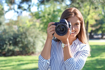 Young female photographer with professional camera in park. Space for text