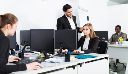 Young  businesswoman working with laptop in office and man colleague helping