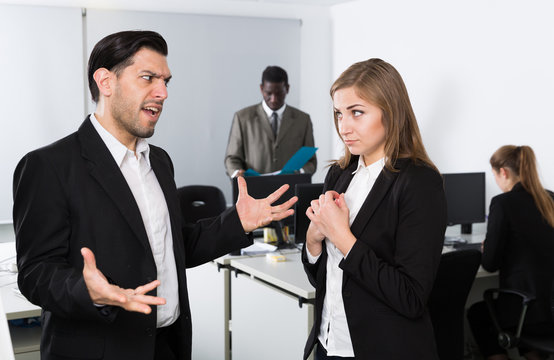 Male boss pointinting to misses in work to woman  manager