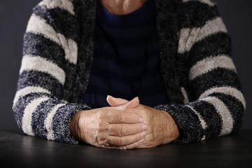 Poor elderly woman sitting at table, focus on hands