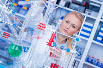 Female laboratory assistant with chemical experiment in scientific laboratory. Female medical or scientific researcher using test tube on laboratory.