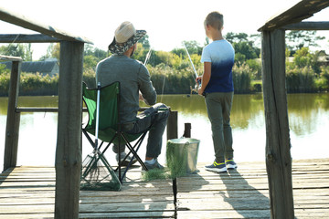 Father and son fishing together on sunny day