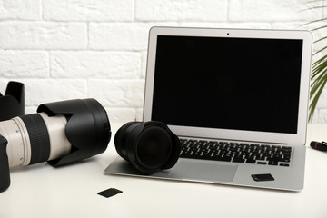 Laptop and professional photographer's equipment on table indoors. Space for text