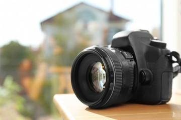 Professional camera on wooden table against blurred background, space for text. Photographer's equipment
