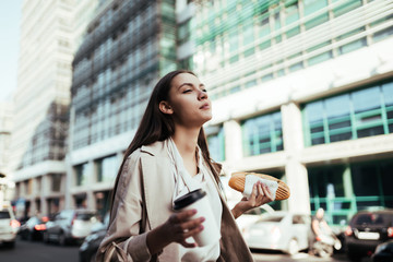 Joyful girl walks down the street and snacks on a sandwich against the background of office buildings