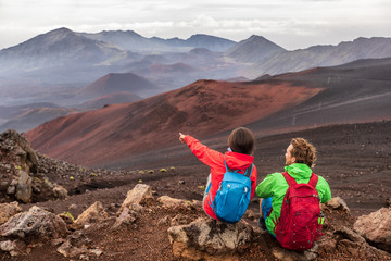 Hiking travel vacation in Maui volcano, Hawaii. USA travel woman with backpack pointing at Haleakala volcano landscape. Couple tourists resting outdoors.