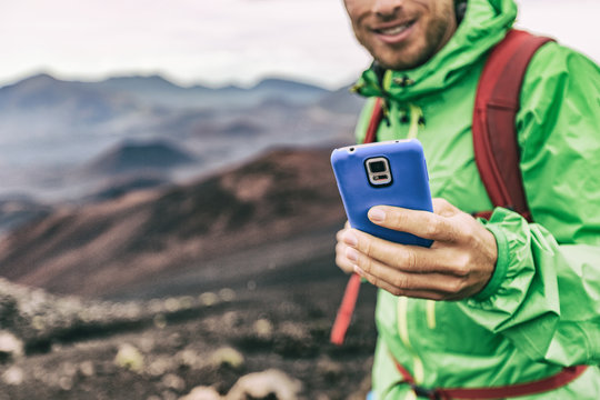 Hiker man taking photo with phone holding blue cover smartphone during outdoor activity in nature landscape. Hiking sport lifestyle young tourist on adventure.