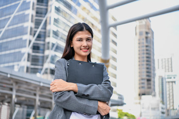 Business concept. Beautiful young businesswoman is working outdoors. Asian girls are working in the business district.