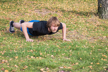Athletic hipster man is doing push-ups in the park.