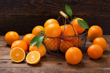 fresh orange fruits in a basket on wooden table Wall mural