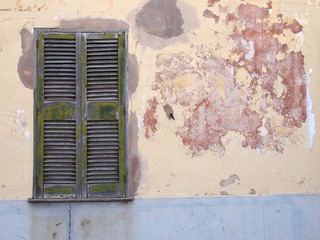 an old cracked house wall with patched cement painted in flaking peeling layers of grey yellow and red paint with a green wooden cracked window with closed shutters
