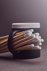 Group of pencils in a black cup, isolated on a gray background.
