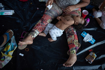 A toddler, part of a caravan of thousands of migrants from Central America en route to the United States, cries as he is wiped by his mother in the Tapachula city center