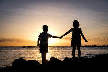 Siblings holding hands at sunset