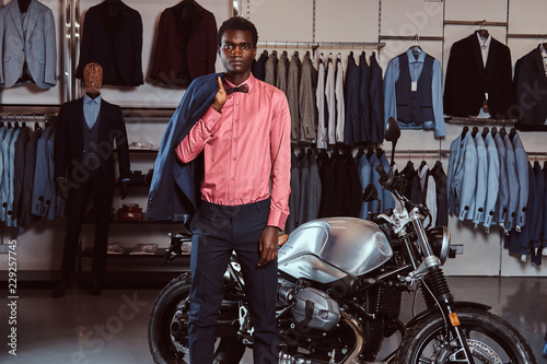 bd9da9d4 African American young man dressed in elegant formal wear posing near retro  sports motorbike at the men's clothing store.