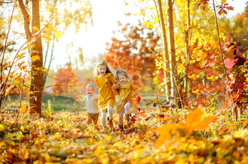 happy kids running and playing in a beautiful autumn park