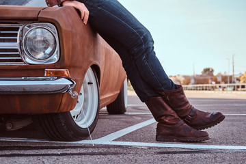 Cropped photo of male in jeans and boots leaning on retro car in the city parking.