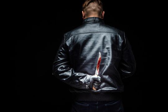 Serial killer maniac holding killer tools behind his back