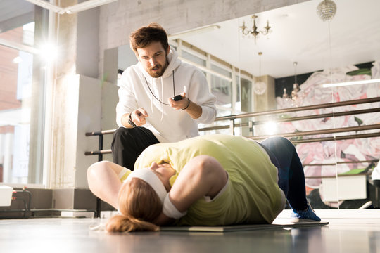 Portrait of obese young woman doing crunches during workout with fitness instructor in sunlight, copy space