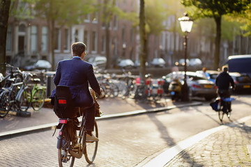 Elegantly dressed man riding a bicycle in historical town of Amsterdam