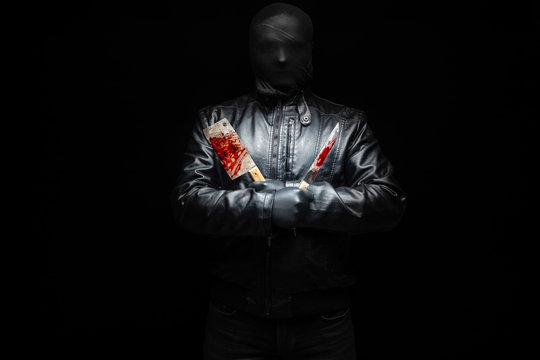 Serial killer hand with bloody killer tools and black gloves