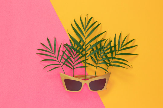 Palm leaves and sunglasses on pink and yellow background