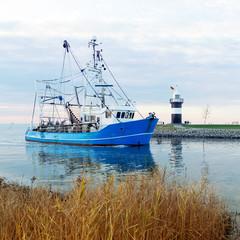 Krabbenkutter zurück im Heimathafen Wremen mit Leuchtturm, Nordseeküste bei Bremerhaven