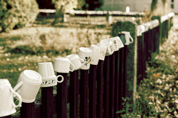 Mugs hanging on the wooden fence, vintage toned picture.
