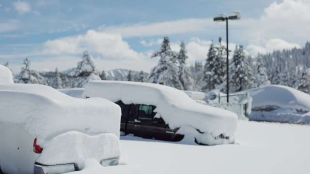 Very snowy parking lot with cars covered in snow for background plate